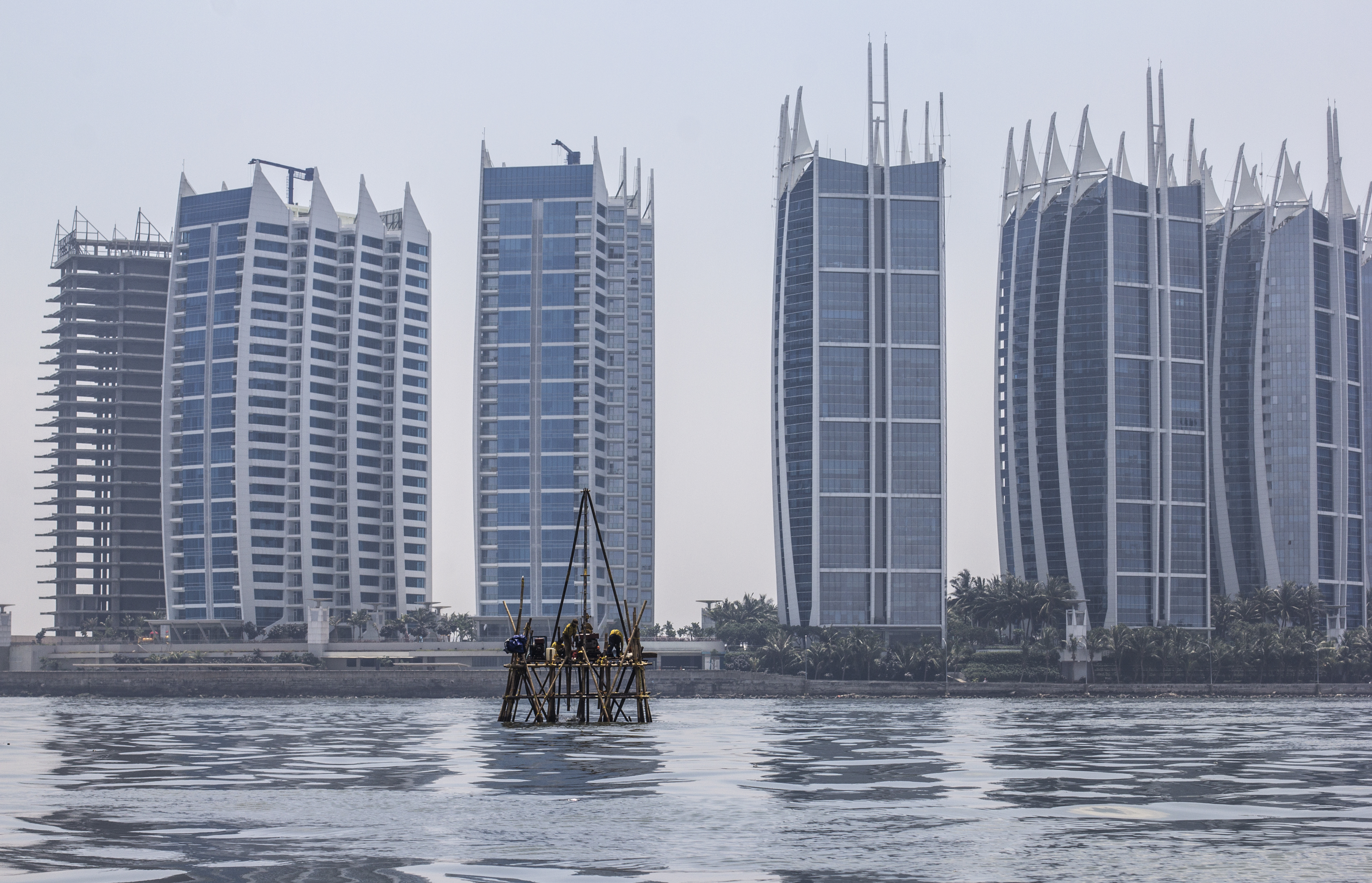 Image of Workers on a bamboo platform take sea floor measurements of Jakarta Bay in front of the massive Regata Development Complex in North Jakarta